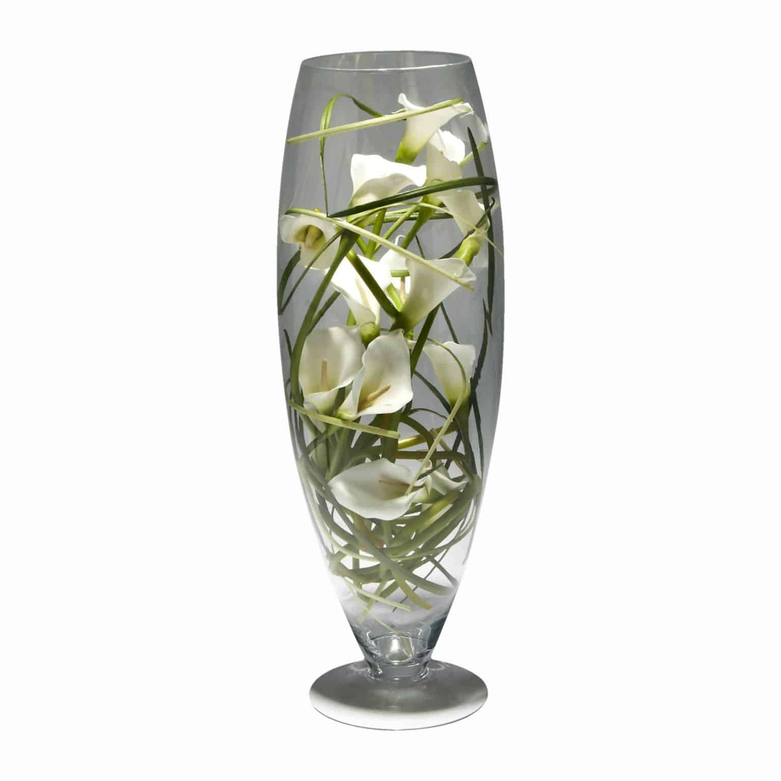 There is no reason to complicate a classic. Buy this luxuriously fine silk flowering calla lilies with meticulous detail arranged in a modern glass vase.
