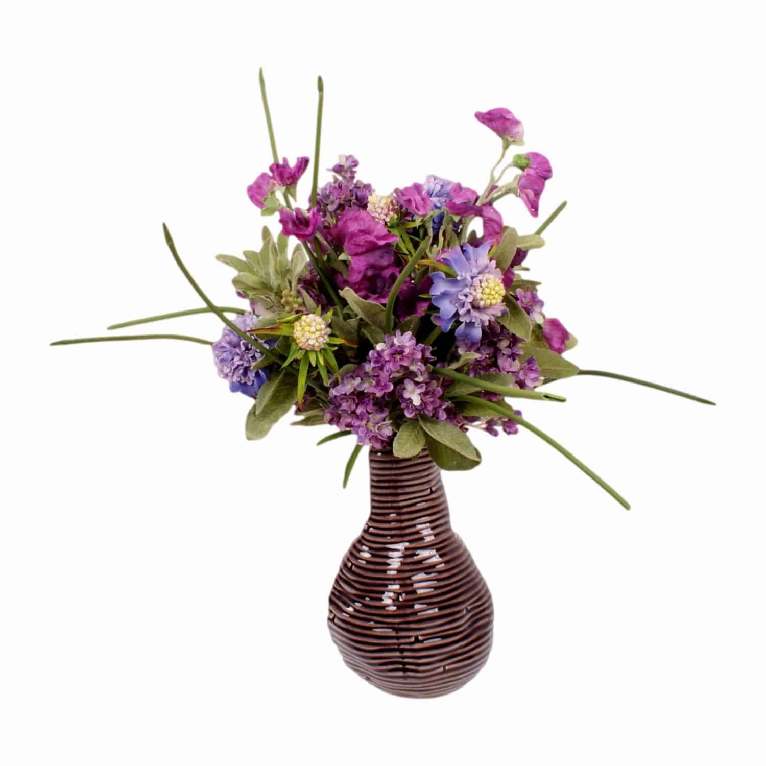 This arrangement will brush away those summer blues. Shop for our silk flowering sweet pea and lilac stems with artificial green leaves.